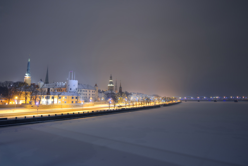 Panorama of night Riga in winter with Daugava river frozen